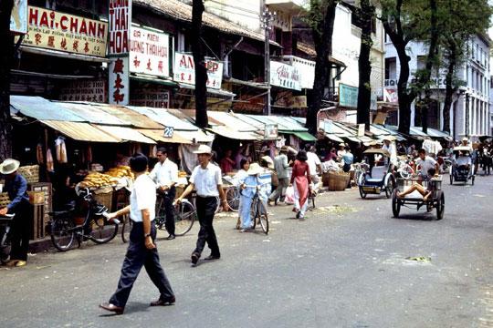 Velosolex Cycle-pousse dans une rue commercante de Saigon